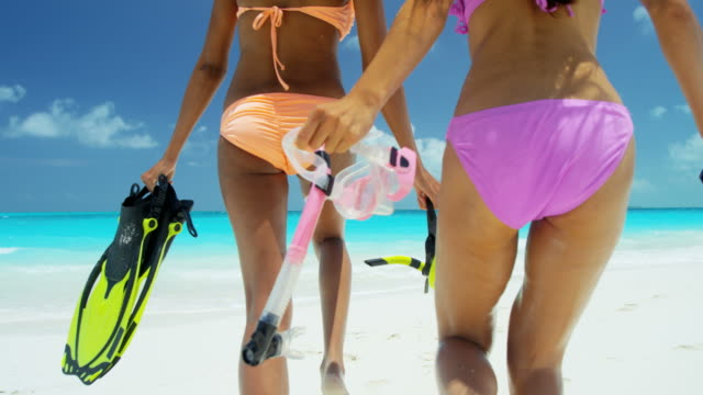 Multi ethnic girls with snorkel equipment on beach