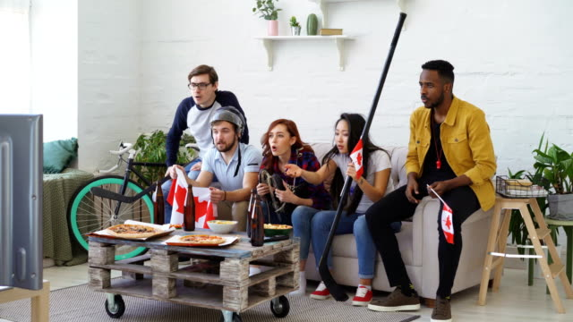 Multi ethnic group of friends sports fans with Canadian national flags watching hockey championship on TV together cheering up their favourite team at home video