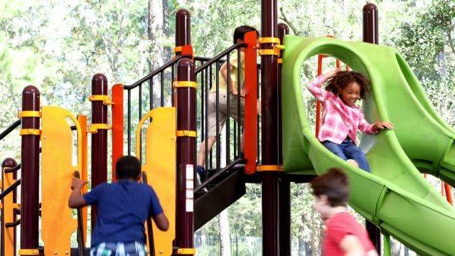 Multi ethnic group of school children playing on school playground. Multi ethnic group of elementary school children are playing, climbing and having fun on the school playground. outdoor play equipment stock videos & royalty-free footage