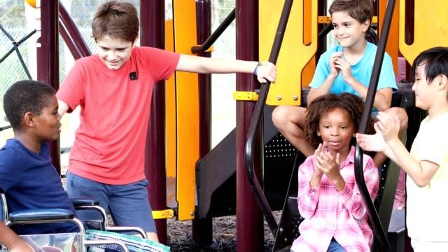 Multi ethnic group of school children playing on school playground. video