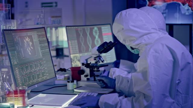covid-19 - многоэтническая лабораторная группа, работающая над коронавирусом. ношение защитных костюмов - биология стоковые видео и кадры b-roll