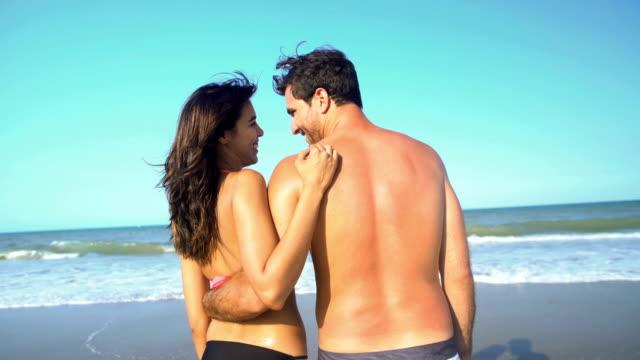 Multi ethnic man and woman relaxing in swimwear video