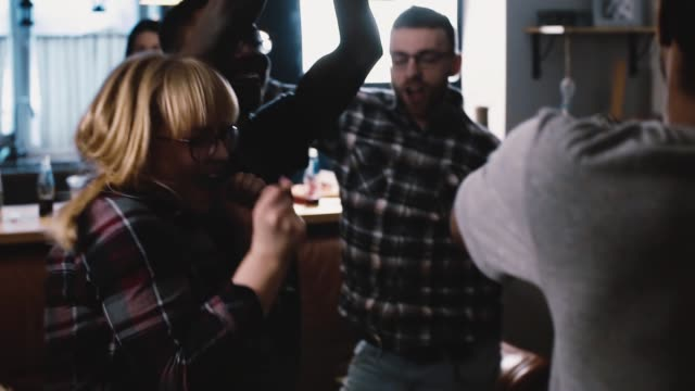 Multi ethnic millennials dance crazy at a party. Slow motion Students get wild and silly at holiday celebration. Emotion video