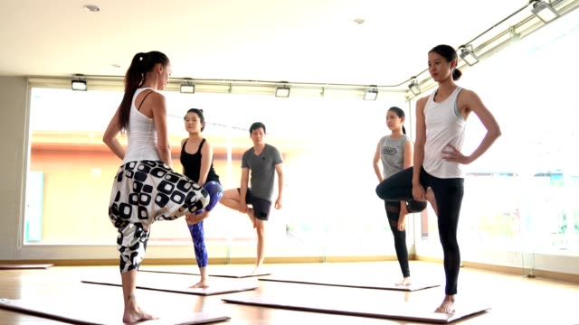 Video multi ethnic people practicing yoga class lead by yoga master
