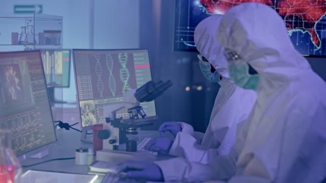 vidéos et rushes de multi ethnic scientists in futuristic laboratory working with biohazardous substance. beaucoup d'infections sur la carte des usa - vaccin covid