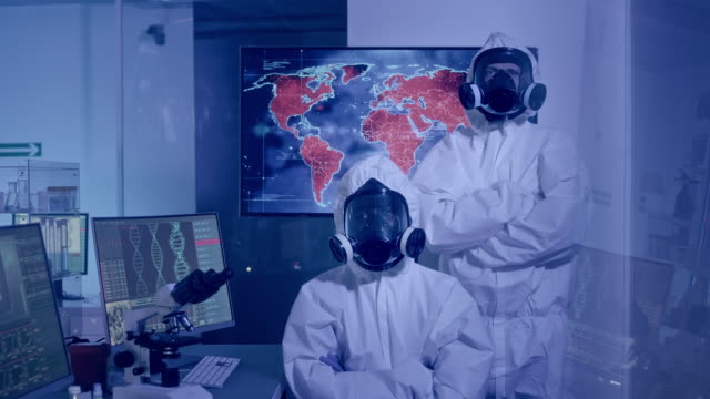 Multi ethnic scientists satisfied with work. Studying pathogen transmission in the world Scientists in clean suits looking at camera. World map in background - high infectivity biosensor stock videos & royalty-free footage