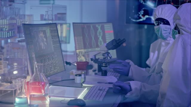 многоэтнические ученые, работающие с биоопасным веществом. защитные костюмы - континент географический объект стоковые видео и кадры b-roll