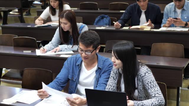 multiethnische studenten beim examen im hörsaal - chinesischer abstammung stock-videos und b-roll-filmmaterial