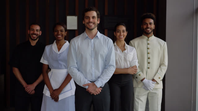 Multi ethnic team at the hotel lobby standing facing camera smiling with a toothy smile