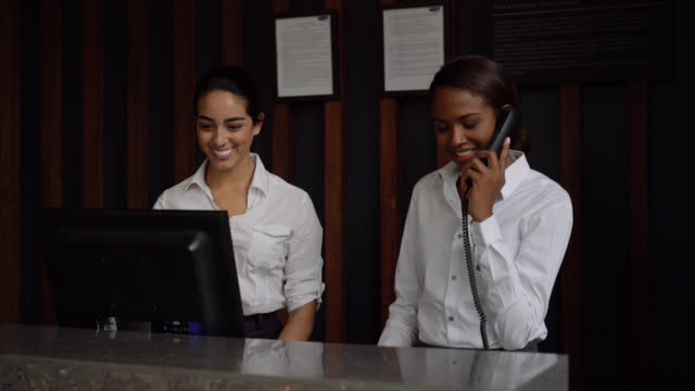 multi ethnic team of receptionist working at the front desk of hotel smiling - hotel checkin video stock e b–roll