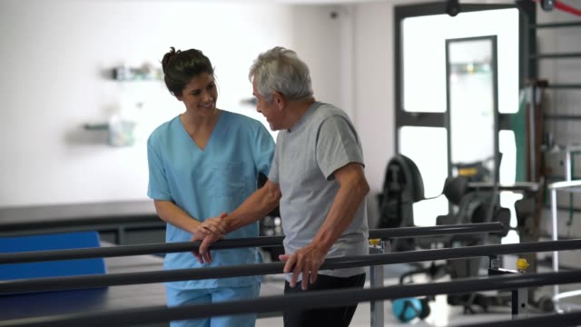 multi ethnic team of therapists at a physical recovery clinic helping patients do their therapy one with a senior man and at the background with a young man - fisioterapia video stock e b–roll