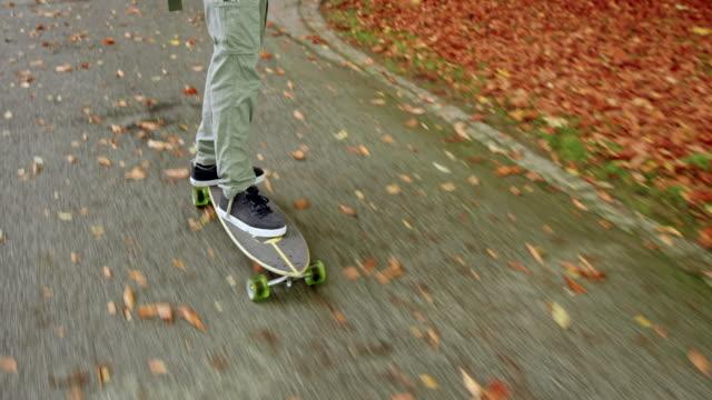 Multi ethnischen junger Mann anhören von Musik während der Fahrt mit seinem Longboard in einem park – Video