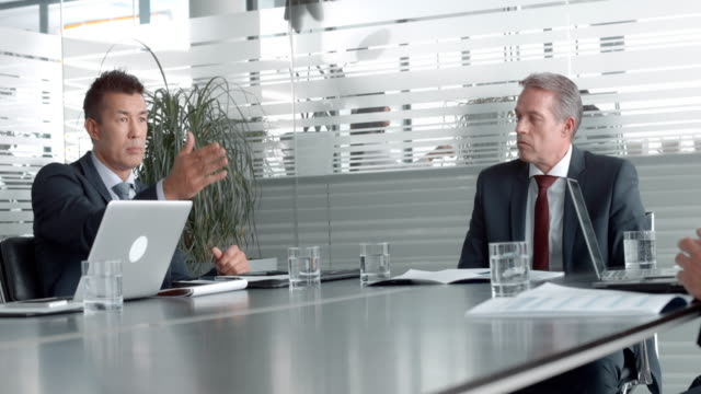Multi ethnical business partners in a meeting with the company's CEO Medium handheld shot of multi ethnical businessmen in a meeting with their CEO in the conference room. Shot in Slovenia. board room stock videos & royalty-free footage