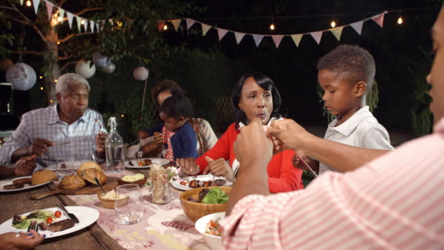 vídeos de stock e filmes b-roll de multi generation black family eating food at table outdoors - etnia filipina