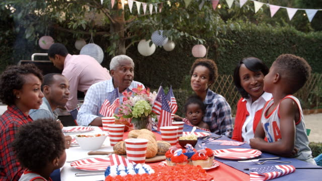 multi generation black family talking at 4th july barbecue - giorno dell'indipendenza video stock e b–roll