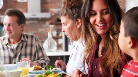 famiglia multigenerazionale che si gode il pasto intorno al tavolo a casa - cena video stock e b–roll