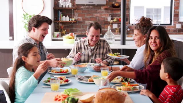vídeos y material grabado en eventos de stock de familia de multi generación disfrutando de comida alrededor de la mesa en casa - cena familiar