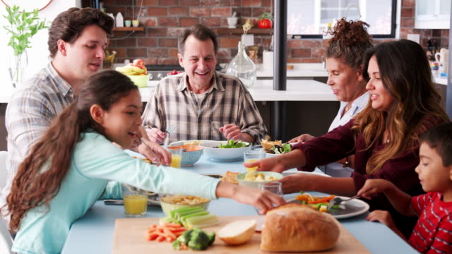 multi generation family enjoying meal around table at home - family video stock e b–roll