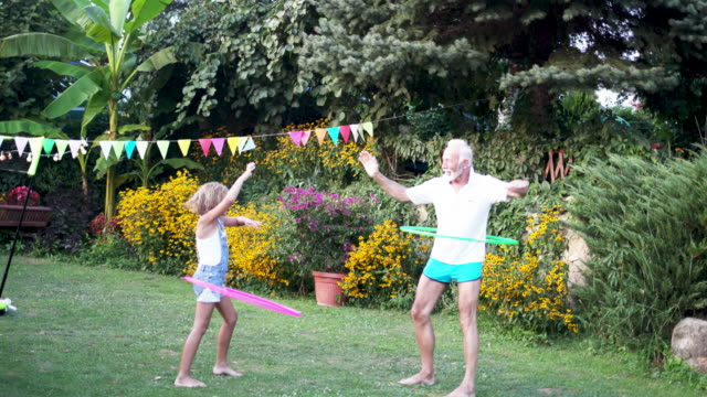 multi generation family hula hooping in back yard - giovane nell'animo video stock e b–roll