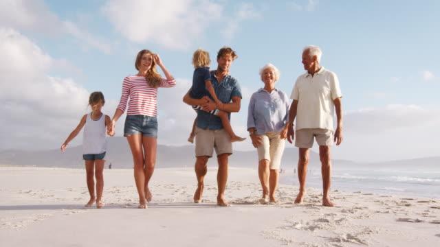 multi generation family on summer vacation walking along beach - nonna e nipote camminare video stock e b–roll