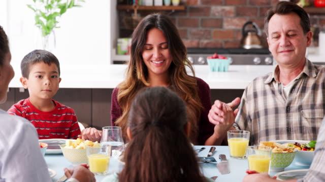 multi generation family praying before meal around table at home - modlić się filmów i materiałów b-roll