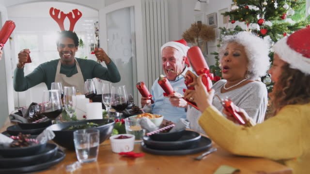 vídeos de stock e filmes b-roll de multi generation family pulling christmas crackers as they sit for meal at table - family christmas