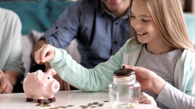 Multi generation family saving money Three generation family is putting money into a piggy bank in their living room. piggy bank stock videos & royalty-free footage