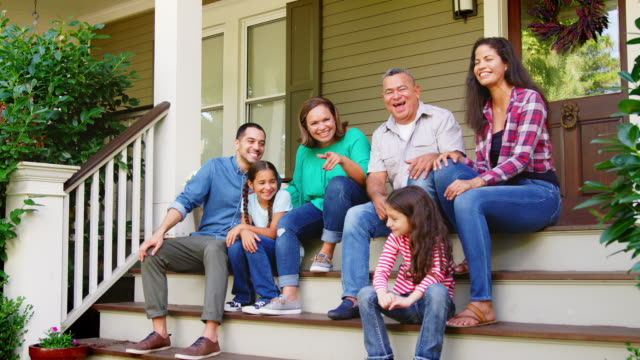 multi generation family sit on steps leading up to house porch - portico video stock e b–roll