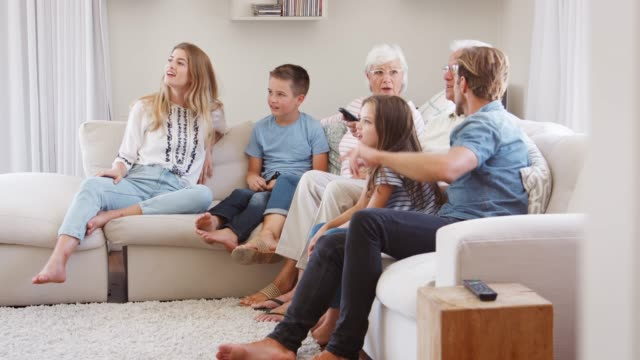 Multi Generation Family Sitting On Sofa At Home Watching TV Slow motion sequence of multi generation family relaxing on sofa at home together and watching television family watching tv stock videos & royalty-free footage