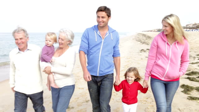 multi-generazione famiglia a piedi lungo la spiaggia insieme - nonna e nipote camminare video stock e b–roll