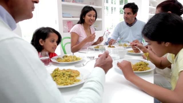 Multi generación familiar India comiendo comida en su hogar - vídeo