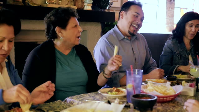 Multi generational Hispanic family enjoying meal together in Mexican restaurant video