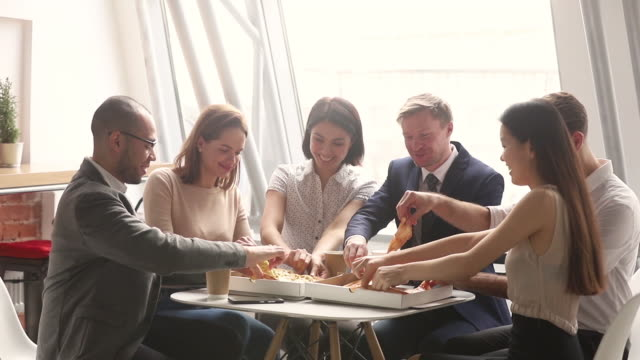 Multi racial colleagues eating lunch pizza during workday