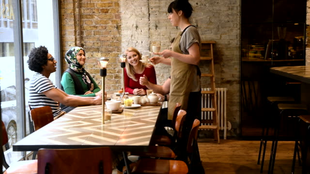 Multi racial group of friends talking in cafe and waitress bringing drinks