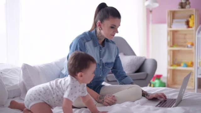 vidéos et rushes de multi tasking mère avec fils travaillant à la maison - femmes actives