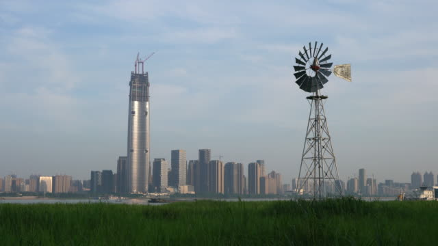Multi-bladed windpump in middle of Hankou marshland and Wuhan city skyline in background in Hubei China