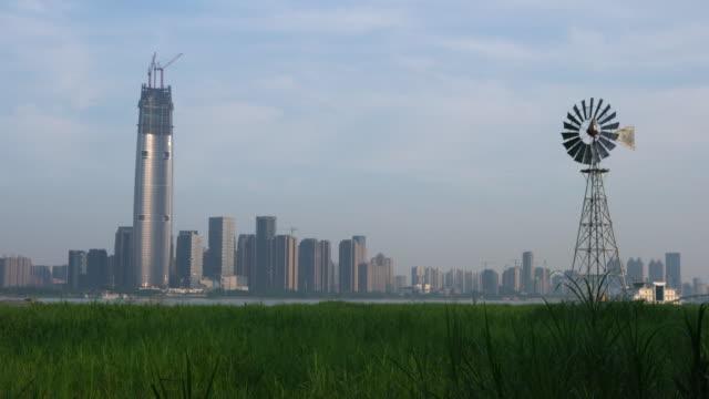 vídeos y material grabado en eventos de stock de bomba de viento multi-bladed en medio de los pantanos de hankou y el horizonte de la ciudad de wuhan en el fondo en hubei china - wuhan