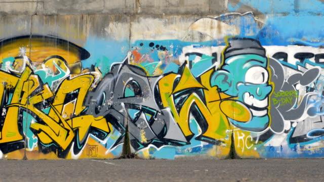 mångfärgade graffiti täcker hela längd en gatan vägg. - väggmålning bildbanksvideor och videomaterial från bakom kulisserna