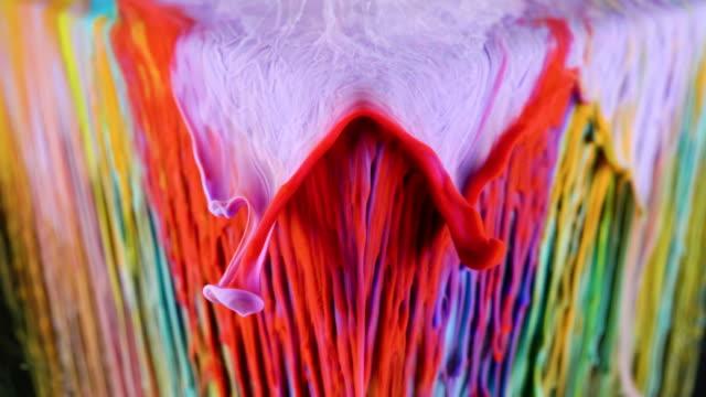 vidéos et rushes de la peinture à l'encre multicolore coule lentement du cube sous l'eau - image composite numérique