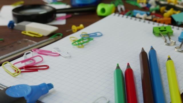 vidéos et rushes de crayons multicolores, trombones et cahier sur le bureau en bois brun - fournitures scolaires