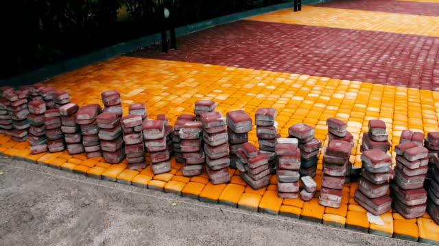 Multicolored sidewalk tiles in children's park lies on the ground ready for laying video