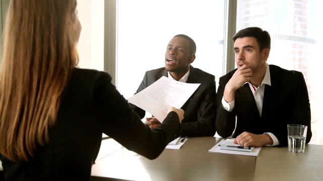 Multicultural businessmen conducting job interview, asking questions to female applicant Multicultural businessmen wearing suits interviewing young lady, searching for a job, listening to female applicant telling about working experience, reviewing resume, asking answering questions job interview stock videos & royalty-free footage