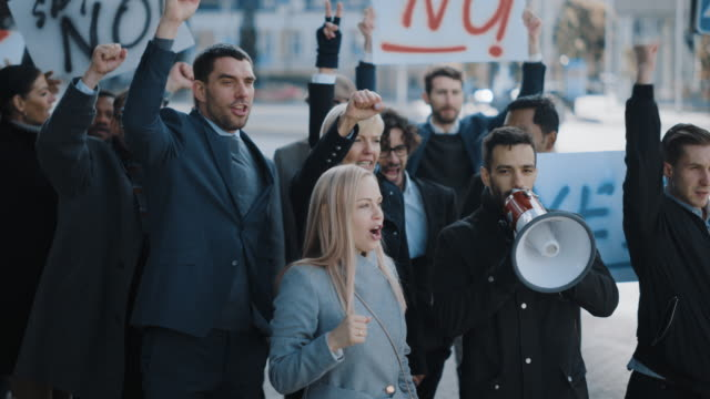 vídeos de stock e filmes b-roll de multicultural diverse office managers and business people picketing outside on a street. men and women screaming for justice, holding a megaphone, picket signs and posters. economic crisis strike. - moralidade