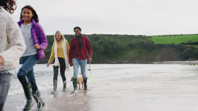 Multi-cultural family with pet dog walking along shoreline on winter beach vacation - shot in slow motion
