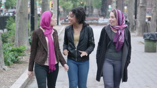 vídeos de stock e filmes b-roll de multi-cultural female friends walk in the city - afro americano