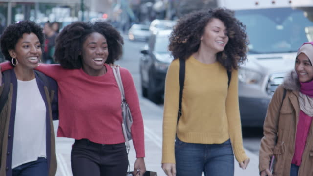 Multi-Cultural Female Friends Walk in the City African-American, mixed race, and Muslim women walk and talk together in the city. group of people stock videos & royalty-free footage