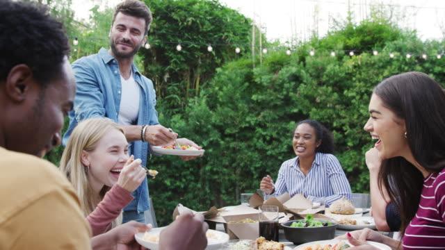 multikulturelle freunde zu hause sitzen am tisch genießen essen bei sommergarten-party - freund stock-videos und b-roll-filmmaterial
