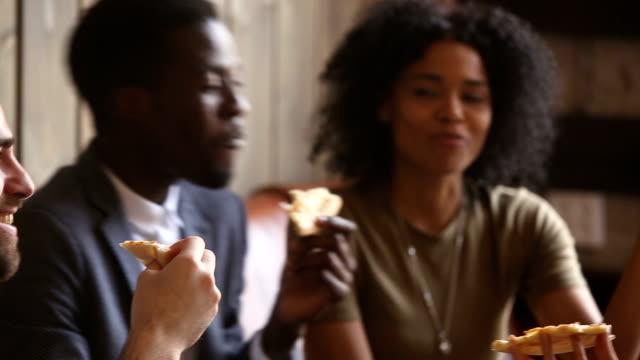 vídeos de stock, filmes e b-roll de multiculturais amigos se divertindo, comendo pizza italiana saborosa a rir juntos - comida feita em casa