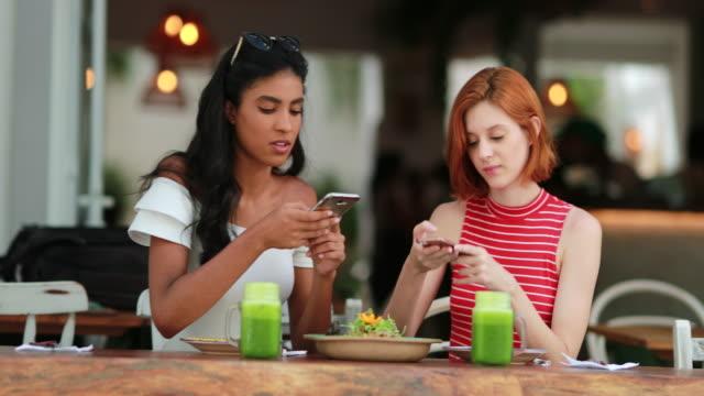 vídeos de stock, filmes e b-roll de garotas multiculturais tirando foto da refeição com dispositivo de celular. amigas sentadas em restaurante - amizade feminina