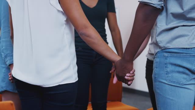 stockvideo's en b-roll-footage met multi-culturele groep mannen en vrouwen de handen ineen op geestelijke gezondheid groep therapie bijeenkomst - geloof